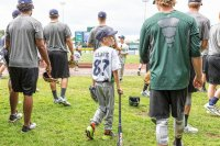 Zander Clark of West Fairlee, VT walks onto Centennial Field in Burlington, VT with players from the Vermont Lake Monsters, minor league baseball team, on Friday, Aug. 14, 2015. (Oliver Parini photograph)